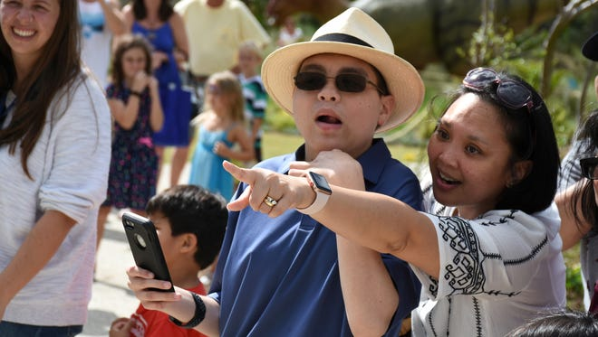 Chad's mother Marve Ann Alaimo points out the signs showing his wish has been granted. Chas Alaimo, 17, had his wish to visit fossil fields in Montana granted through Make-A-Wish, during a visit to the Naples Botanical Garden Saturday.