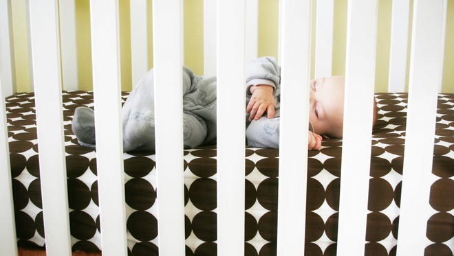 Getty Images/iStockphoto Sleeping baby inside a crib. Demonstrates safe sleep for infants with no blankets or bumper pads.