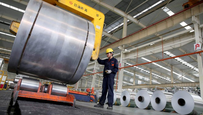 A Chinese worker checks aluminium tapes at an aluminium production plant in Huaibei, east China's Anhui province in May 2017.
