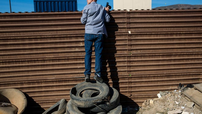 John Thurston peers over the border fence, standing atop tires while with a tour group hosted by MAGA/Hauser & Wirth to view the border wall prototypes along the U.S. Mexico Border on February 1, 2018 in Tijuana, B.C., Mexico. Christoph Buchel, a Swiss-Icelandic artist, and the group MAGA has proposed the prototypes be protected as a national monument. (Kent Nishimura/Los Angeles Times/TNS)