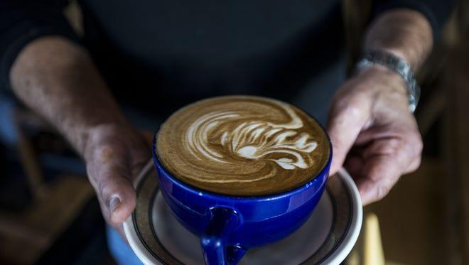 Owner Daniel Wayne holds a latte at Lola Coffee in Phoenix.