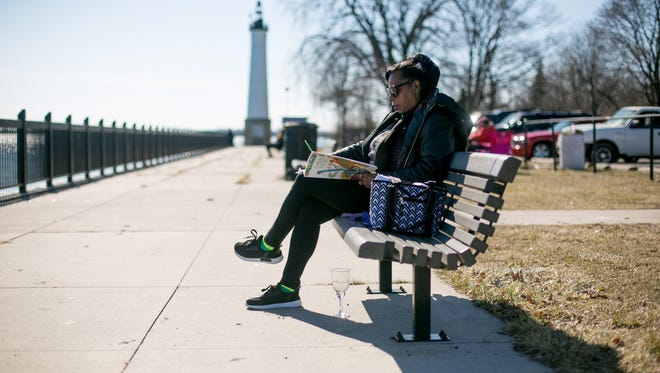 Cathy Coleman, 62, of Detroit draws in Mariner Park in Detroit Sunday.