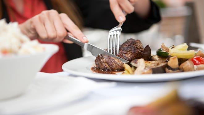 File photo of person cutting steak.