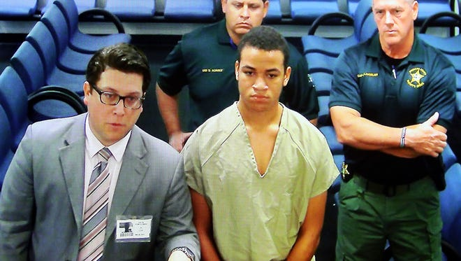 Zachary Cruz, center, the brother of the Florida school shooting suspect, is displayed in a monitor via closed circuit television from the main jail as he as he makes his first appearance on charges of trespassing on the grounds of Marjory Stoneman Douglas High School, Tuesday, March 20, 2018, at the Broward County Courthouse in Fort Lauderdale, Fla. A judge set an unusually high $500,000 bond on Tuesday and imposed a host of other restrictions.