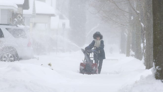A resident plows snow on her sidewalk Tuesday in Wausau, Wisc. T'xer Zhon Kha/USA TODAY NETWORK-Wisconsin