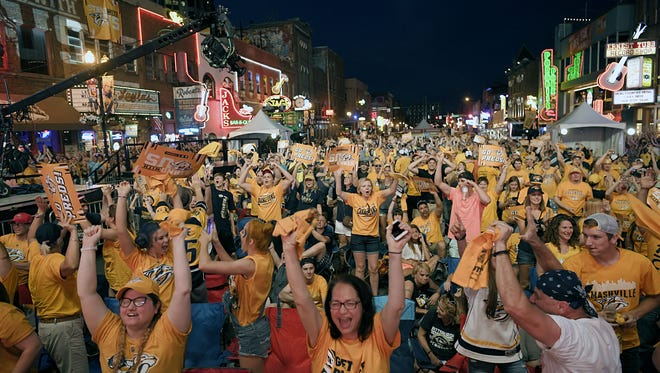 Predators fans on lower Broadway celebrate after Nashville scores their fourth goal against Pittsburg during the Stanley Cup final in Nashville on Saturday, June 3, 2017.  Lower Broadway was closed for a watch party.