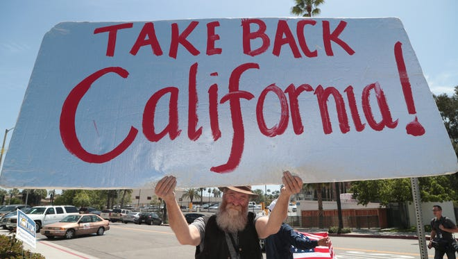 Matthew Woods holds up a sign with counter-protesters at the Unite Inland Empire Conservative Conference in Riverside, Calif., Sunday, April 8, 2018.