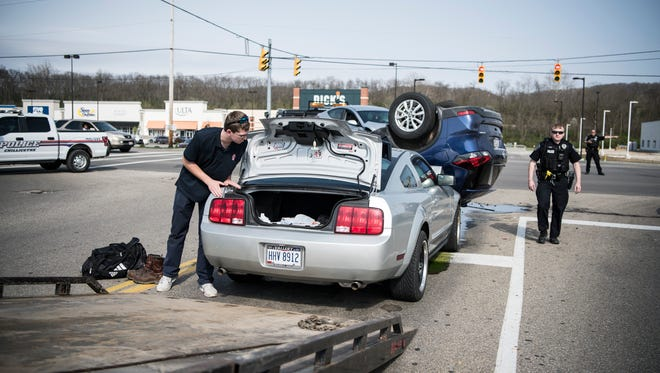 Michael Hayes removes items from the trunk of his Mustang before his car is towed after being hit by a Nissan Rogue while stopped at the stop light at the intersection of North Bridge Street and the access road to Sam's Club in Chillicothe Wednesday evening.