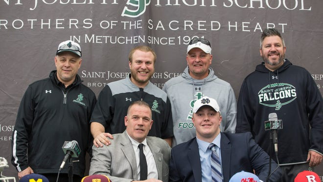 Olmstead sits with the St. Joseph High School football team coaching staff. John Olmstead commits to Notre Dame for his college football career. The announcement was made with friends, family, and teammates at St. Joseph High School.  