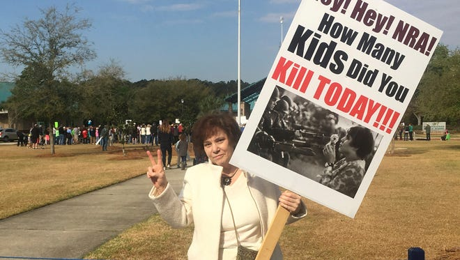 """In this March 24, 2018 photo, Jan Rose Kasmir holds a sign with a photo of her offering a flower to soldiers in a 1967 protest against the Vietnam War, during a rally for gun safety laws in Bluffton, S.C. Kasmir gave up protesting when public opposition failed to stop the Iraq War in 2003. But after the 2017 Women's March, she returned to the lines this spring to rally for gun control near her home in Hilton Head, South Carolina, joining a series of recent protests by millions of Americans demanding change. """"I think we've reached a tipping point,"""" Kasmir said."""