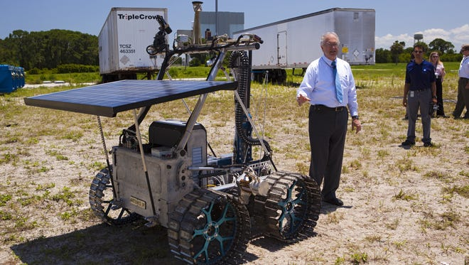 In June 2012, NASA In-Situ Resource Utilization Project Manager Bill Larson discusses the design and operation of the prototype rover Artemis Jr. for NASA's RESOLVE project -- later renamed Resource Prospector -- during a rover demonstration in a field beside the Operations and Checkout Building at Kennedy Space Center.