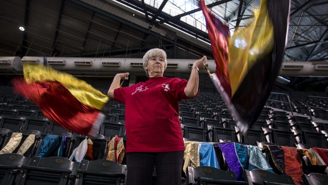 """Cindy McBride, more commonly known as the """"Flag Lady,"""" twirls her flags before the Diamondbacks game against the Brewers on Wednesday, May 16, 2018 at Chase Field in Phoenix."""