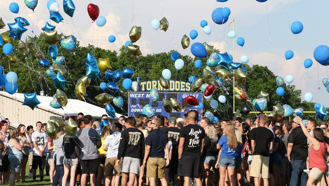 Friends and family release balloons in memory of Cameron Strauss during a vigil in his honor on Tuesday.
