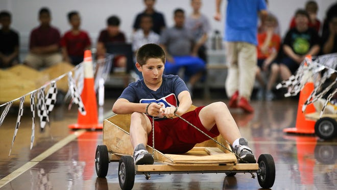 Blaine Preher pilots his soap box derby racer at Olmsted Academy North during a heat race.  The races, held in one of the school's gymnasiums, was the culmination of a year-end project that had each team constructing a car from scratch.
