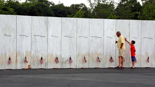 Visitors to the Flight 93 National Memorial pauses at the Wall of Names containing the names of the 40 passengers and crew of United Flight 93 that were killed in this field on Sept. 11, 2001, on Thursday, May 31, 2018. Later this year, the remaining wreckage of Flight 93 will be returned to the Flight 93 National Memorial to be buried in the restricted access zone, in the woods beyond the Wall of Names marked by a giant boulder, where they will not be accessible to the public or media. (AP Photo/Gene J. Puskar)