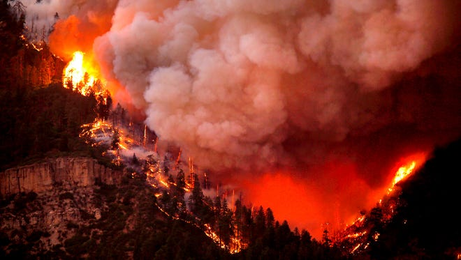 In this photo taken Wednesday, the 416 Fire burns down Hermosa Cliffs above U.S. Highway 550 on the southeast side of the fire near Hermosa, Colo. (Jerry McBride/Durango Herald via AP)/The Durango Herald via AP)
