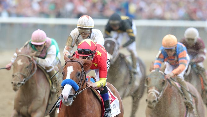 Mike Simth aboard Justify (1) leads the pack down the straightaway during the running of the 150th Belmont Stakes at Belmont Park on June 9.