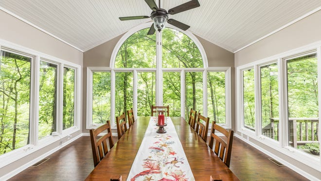 The dining room appears to float in the woods at 10421 Fall Creek Road.