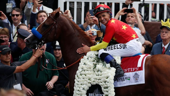 Mike Smith aboard Justify (1) poses for photos in the winner circle after winning the 150th Belmont Stakes to become the 13th Triple Crown winner.