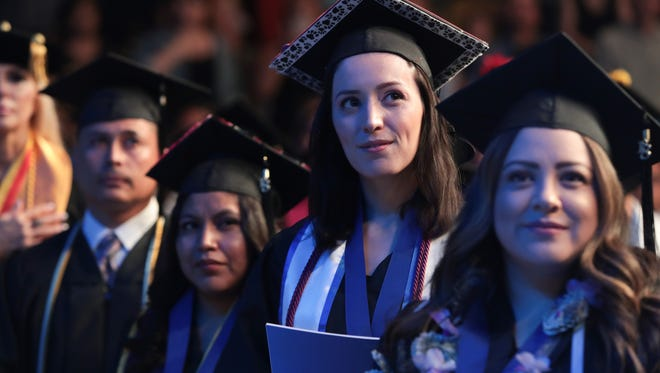 Graduates listen to Cherie Denise Bowman as she sings the national anthem at the Cal State University San Bernardino, Palm Desert Campus commencement ceremony, Rancho Mirage, Calif., Thursday, June 14, 2018.