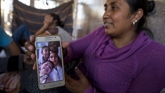Guadalupe Arcos Avila, 34, of the state of Guerrero, shows a picture of her family on Wednesday, June 20, 2018, at the DeConcini Port of Entry in Nogales, Sonora, Mexico. She has been waiting for an asylum interview with U.S. immigration officials for nine days.