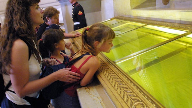 Visitors look at the original copies of the Declaration of Independence, the Constitution and the Bill of Rights on July 4, 2001, at the National Archives in Washington, D.C.