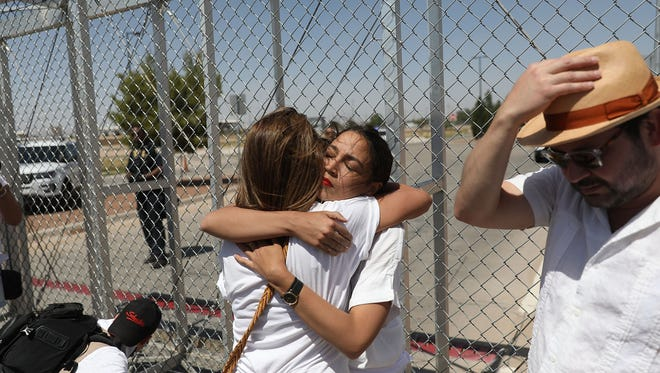 "Alexandria Ocasio-Cortez is embraced at the Tornillo-Guadalupe port of entry gate on June 24, 2018, in Tornillo, Texas, where she was protesting the separation of children from their parents after they were caught entering the U.S. under the administration's ""zero tolerance"" immigration policy."