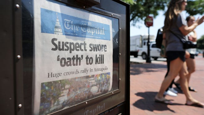A newspaper vending machine sells copies of the Capital Gazette, with stories about last week's shooting at the community newspaper's office.