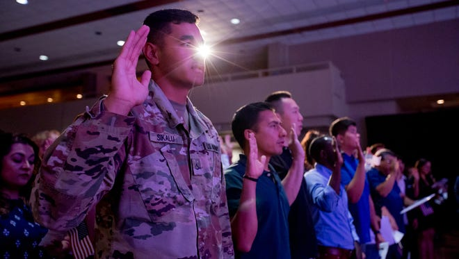 """Taniela Sikalu, originally of Tonga and now residing in Mesa, takes the Naturalization Oath of Allegiance during a July 4 ceremony at Mesa's Celebration of Freedom Wednesday.  """"I'm just excited and proud to be an American,"""" Sikalu said."""