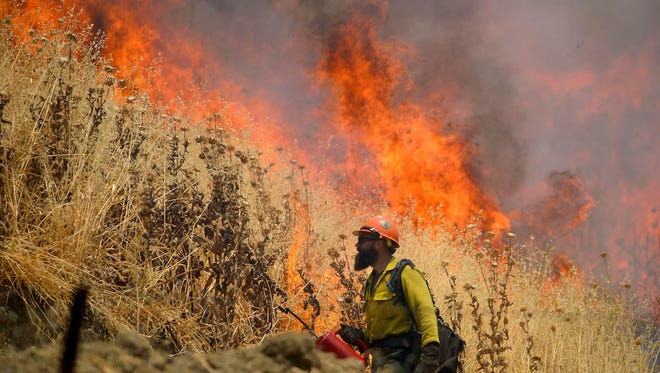 Hot Shot crews from Mendocino use backfires to help contain the County Fire along Highway 129 near Lake Berryessa in Yolo County, California, on July 3, 2018.