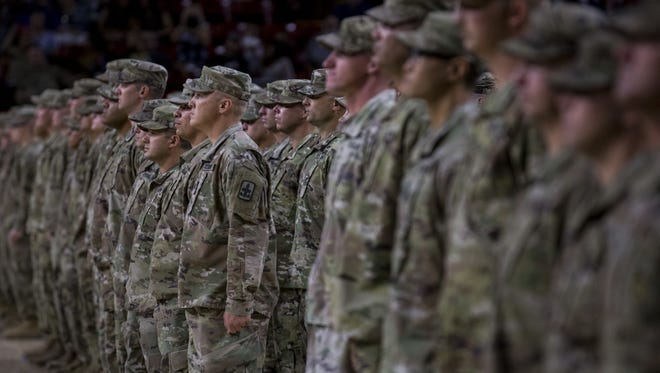 Members of the Arizona Army National Guard 1st Battalion, 158th Infantry Regiments stand at attention during their deployment ceremony on Saturday, July 7, 2018, at Wells Fargo Arena in Tempe, Ariz.