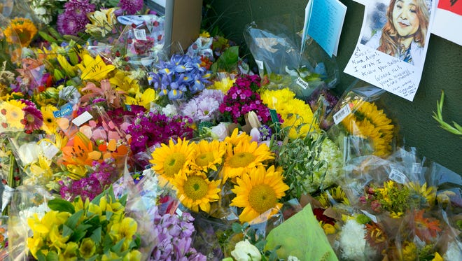 A note with the likeness of Trader Joe's employee Melyda Corado is surrounded by flowers, candles and support notes growing on the sidewalk outside the Silver Lake Trader Joe's store in Los Angeles on Monday. Trader Joe's worker Corado was shot and killed in an exchange of gunfire between a suspect and the police at the store.