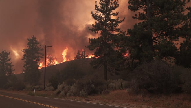 Less than one day after it was started, the smoke plumes and embers rose above Highway 74 between Mountain Center and Lake Hemet, Thursday, July 26, 2018.