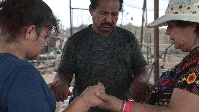 Laura Rodelo Lopez, left, prays with her parents, Natividad and Margarita Armijo as they work to rebuild their home that burned down on the Torres-Martinez Reservation, July 31, 2018.