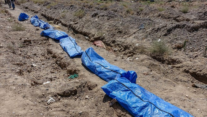 The Raqqa Civil Council Emergency Team has lined the remains of victims of the Islamic State at a makeshift burial site at Raqqa's zoo. Teams are working to find thousands of missing people.