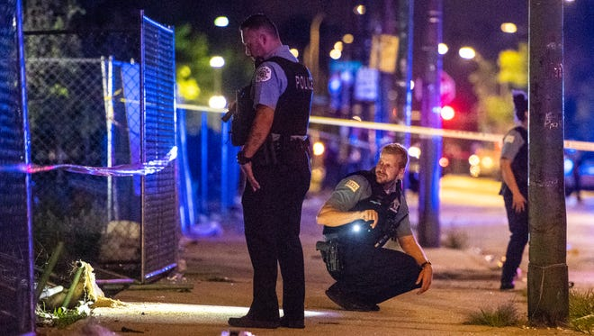 Police investigate the scene where multiple people were shot in Chicago on Aug. 5.