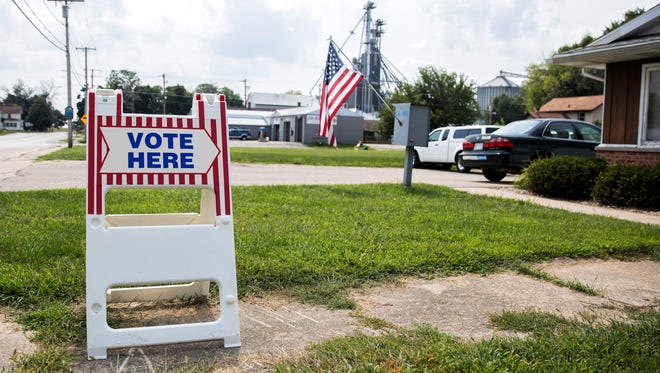 A voting sign is seen outside the town hall in Lake Mills, Wis., on Aug. 14. Cybersecurity experts warn that private vendors, modems and removable memory devices make the state's decentralized voting system vulnerable to attack.