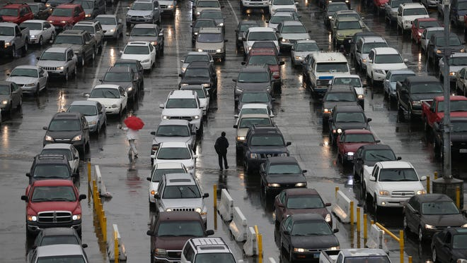 In this Dec. 3, 2014 file photo, cars wait to enter the United States from Tijuana, Mexico through the San Ysidro port of entry in San Diego. San Diego police say a 40-year-old man died after a border inspector shot him with a stun gun at the nation's busiest crossing.