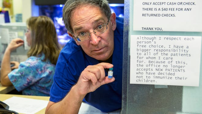 Pediatrician Charles Goodman poses for photo with the MMR vaccine, an immunization vaccine against measles, mumps, and rubella at his practice in Northridge, Calif., Thursday, Jan. 29, 2015.