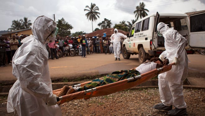 In this Wednesday, Sept. 24, 2014 file photo, healthcare workers load a man suspected of suffering from the Ebola virus onto an ambulance in Kenema, Sierra Leone.