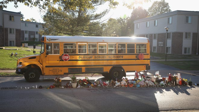A school bus drives by a memorial built on the spot where Michael Brown died in Ferguson, Mo.