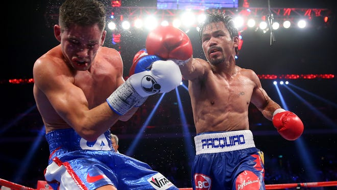 Manny Pacquiao  punches Chris Algieri  during the WBO world welterweight title fight Saturday. Pacquiao says he wants Floyd Mayweather next.