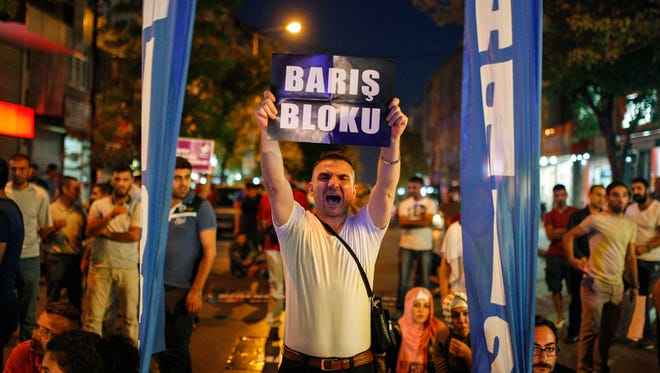 """A man protesting Turkey's operations against Kurdish militants holds a sign that reads in Turkish: """"Peace Block,"""" in Istanbul, on Aug. 19, 2015."""