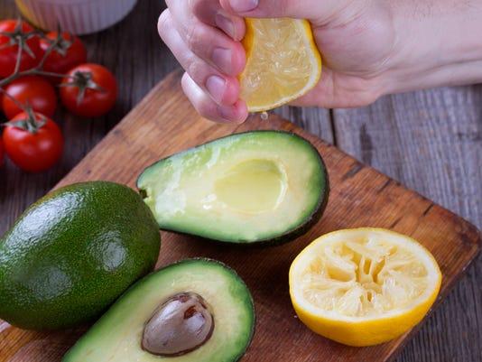 Man hand squeezing lemon on avocado