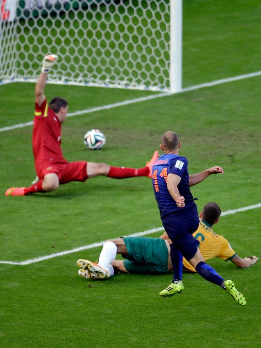 Netherlands' Arjen Robben, front, scores the opening goal past Australia's Matthew Spiranovic, right, and Australia's goalkeeper Mat Ryan, back, during the group B World Cup soccer match between Australia and the Netherlands at the Estadio Beira-Rio in Porto Alegre, Brazil, Wednesday, June 18, 2014.  (AP Photo/Michael Sohn)