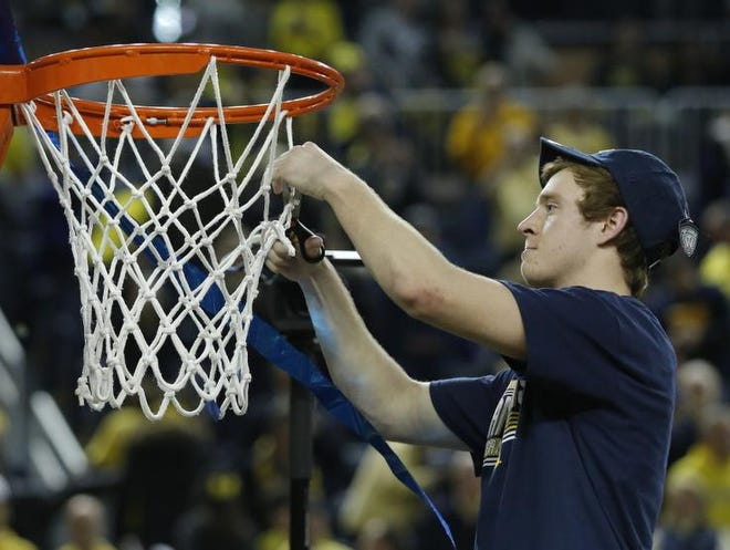 Spike Albrecht #2 of the Michigan Wolverines cuts the net following a 84-80 win over the Indiana Hoosiers on March 8, 2014, in Ann Arbor, Michigan. (Photo by Duane Burleson/Getty Images)