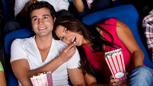 Hispanic couple enjoying popcorn at movie theater