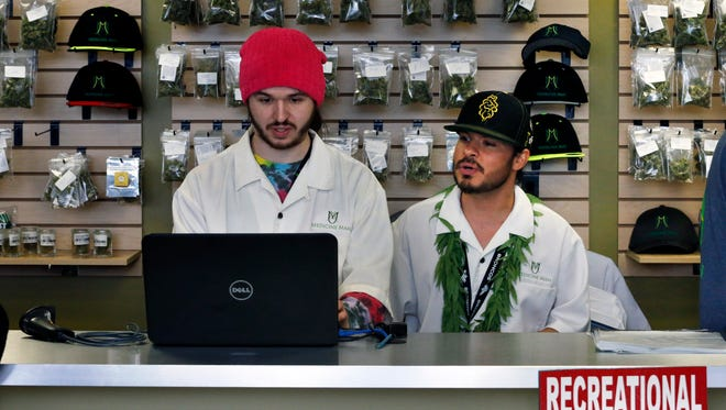 Employees David Marlow, right, and Chris Broussard work behind sales counter inside Medicine Man marijuana retail store, which opened as a legal recreational retail outlet in Denver on Wednesday Jan. 1, 2014.