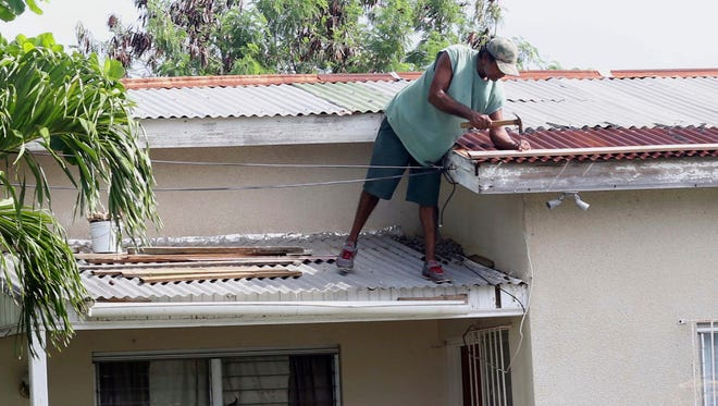 A homeowner makes last minute repairs to his roof in preparation for Hurricane Irma, in St. John's, Antigua and Barbuda, Tuesday, Sept. 5, 2017.  Irma grew into a dangerous Category 5 storm, the most powerful seen in the Atlantic in over a decade, and roared toward islands in the northeast Caribbean Tuesday on a path that could eventually take it to the United States. (AP Photo/Johnny Jno-Baptiste)