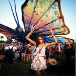 Alessandra Ambrosio gets up close and personal with a massive, multicolored butterfly at the Coachella Music Festival.